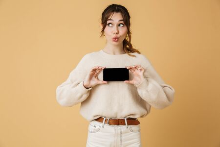 Beautiful cheerful young woman wearing sweater standing isolated over beige background, presenting blank screen mobile phone 스톡 콘텐츠