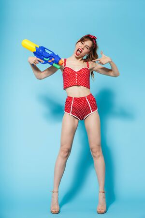 Attractive young slim woman wearing swimsuit standing isolated over blue background, playing with water gun