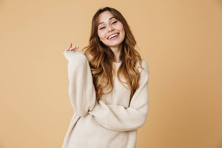 Beautiful young woman wearing sweater standing isolated over beige background Banco de Imagens - 125181604