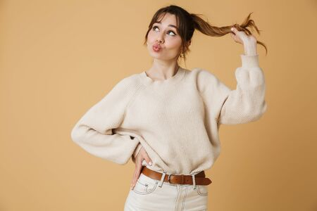 Beautiful young woman wearing sweater standing isolated over beige background