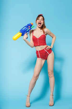 Attractive young slim woman wearing swimsuit standing isolated over blue background, playing with water gun Imagens