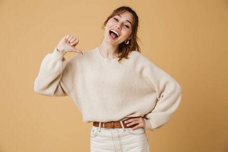 Beautiful young woman wearing sweater standing isolated over beige background Banco de Imagens - 125181635