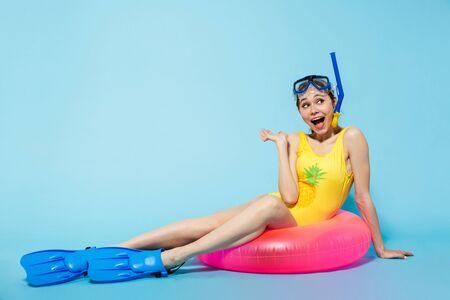 Belle jeune femme portant un maillot de bain s'amusant à la plage avec un anneau gonflable isolé sur fond bleu, portant des palmes et un masque de plongée