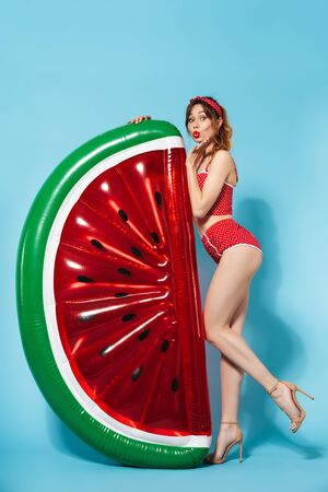 Image of a beautiful young pin up pretty summer girl in swimwear posing isolated over blue background with watermelon air-matress bed. 免版税图像