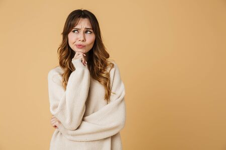 Beautiful upset young woman wearing sweater standing isolated over beige background