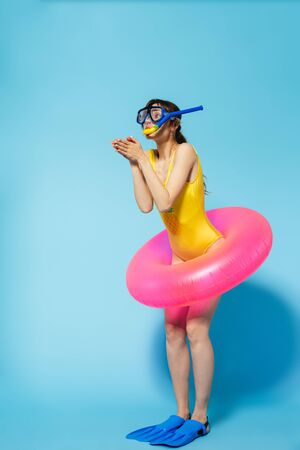 Beautiful young woman wearing swimsuit having fun at the beach with inflatable ring isolated over blue background, wearing flippers and snorkeling mask