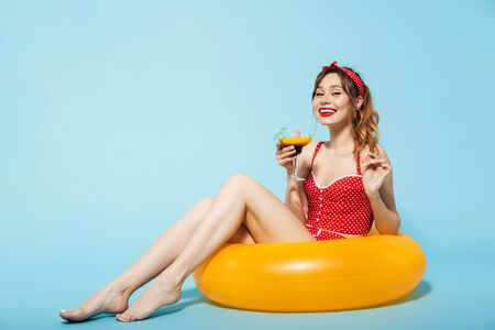 Image of a beautiful young pin up pretty summer girl in swimwear posing isolated over blue background in inflatable ring drinking cocktail.