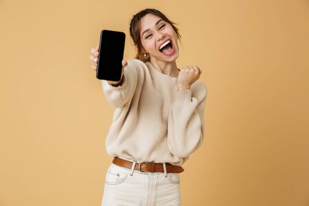 Beautiful cheerful young woman wearing sweater standing isolated over beige background, presenting blank screen mobile phone Stok Fotoğraf