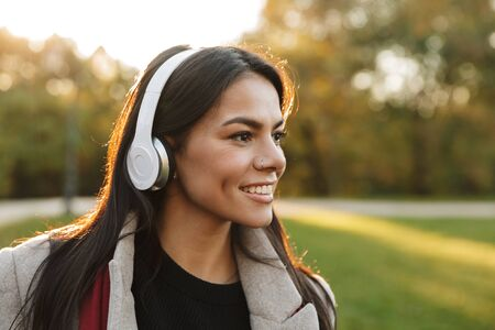 Portrait of happy beautiful woman wearing coat listening to music with headphones and smiling while walking in autumn park
