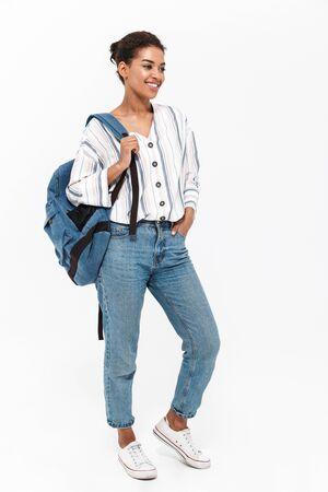 Longitud total de una atractiva joven africana vistiendo ropa casual que se encuentran aisladas sobre fondo blanco, llevando mochila