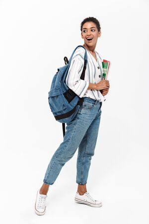 Full length of an attractive young african woman wearing casual clothes standing isolated over white background, carrying backpack, holding textbook