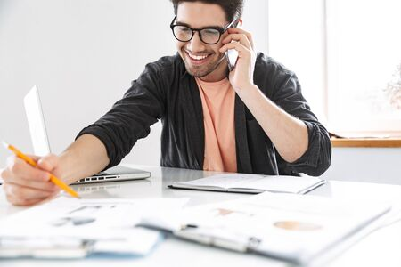 Cheerful handsome man in eyeglasses talking by smartphone and working with documents while sitting by the table at office
