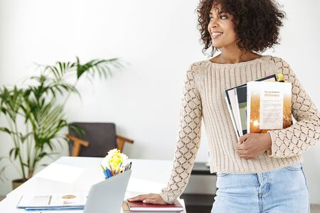 Cheerful african woman wearing in casual clothes holding magazines and looking away while standing near the table at office