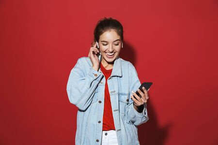 Portrait of a cheerful stylish young woman wearing denim jacket standing isolated over red background, listening to music with wireless earphones, singing