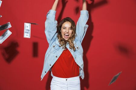 Portrait of a cheerful stylish young woman wearing denim jacket standing isolated over red background, standing under money banknotes rain Standard-Bild - 127397716