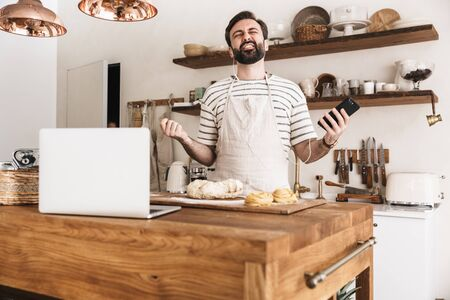 Portrait of joyful brunette man 30s wearing apron using smartphone while cooking and making homemade pasta in kitchen at home