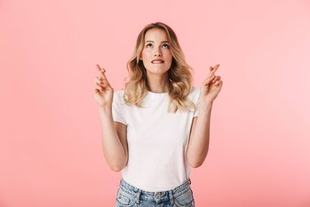 Image of a beautiful concentrated young blonde woman posing isolated over pink wall background showing hopeful please gesture fingers crossed. 版權商用圖片