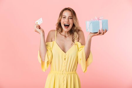 Image of a beautiful excited emotional happy young blonde woman posing isolated over pink wall background holding present gift box and credit card.