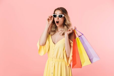 Image of a beautiful shocked young blonde woman posing isolated over pink wall background holding shopping bags.