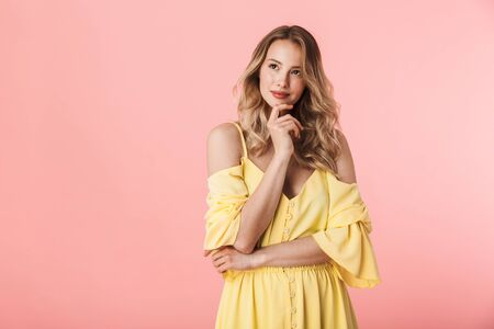 Image of a thinking beautiful happy young blonde woman posing isolated over pink wall background.