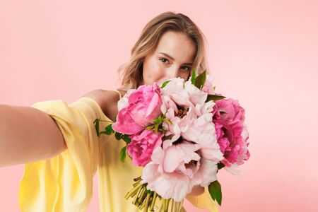 Image of a beautiful amazing young blonde woman posing isolated over pink wall background holding flowers take a selfie by camera.