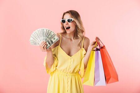 Immagine di una bella giovane donna bionda felice eccitata che posa isolata sopra il fondo rosa della parete che tiene le borse della spesa e i soldi. Archivio Fotografico