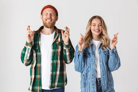 Image of a nervous emotional young loving couple posing isolated over white wall background make hopeful please gesture.