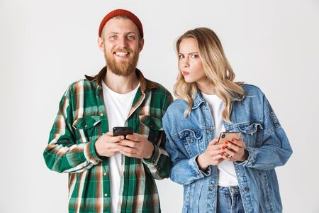 Excited curious young stylish couple standing isolated over white background, using mobile phone