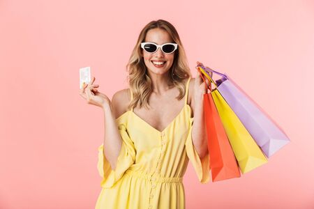 Image of a beautiful excited happy young blonde woman posing isolated over pink wall background holding shopping bags and credit card.