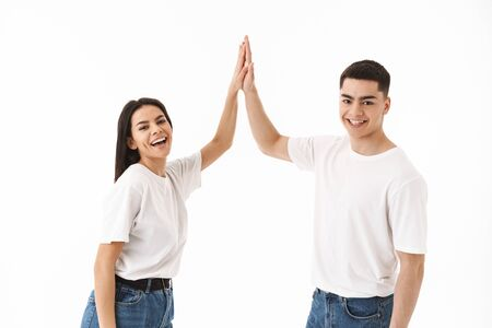 Attractive young couple standing isolated over white background, high five
