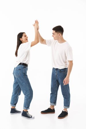 Full length portrait of a young attractive couple standing isolated over white background, high five