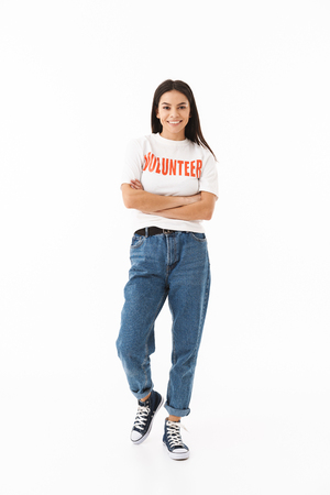 Smiling young girl wearing volunteer t-shirt standing isolated over white background
