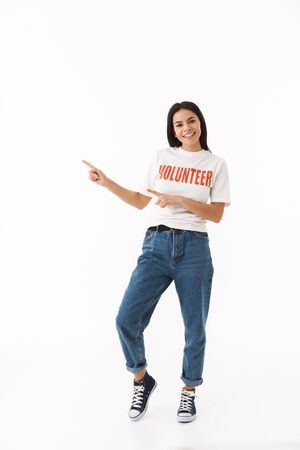 Smiling young girl wearing volunteer t-shirt standing isolated over white background, pointing finger at copy space 写真素材