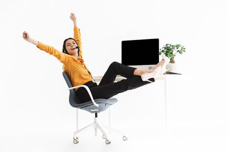 Image of lovely phone operator woman wearing microphone headset rejoicing while sitting at her workplace in office