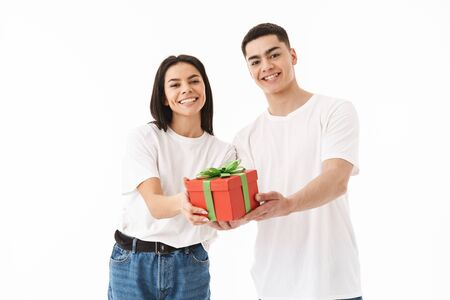 Attractive young couple standing isolated over white background, showing present box