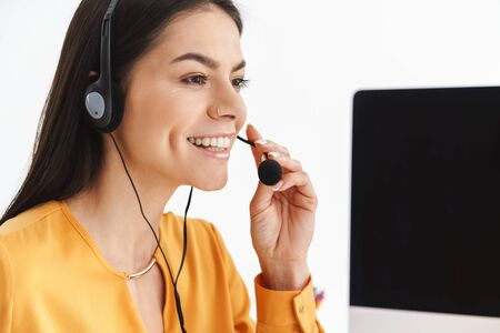 Photo of beautiful phone operator woman wearing microphone headset sitting at her workplace in office and speaking with client