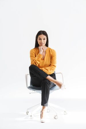 Portrait of gorgeous young businesswoman dressed in elegant wear smiling and sitting in chair while working in bright office