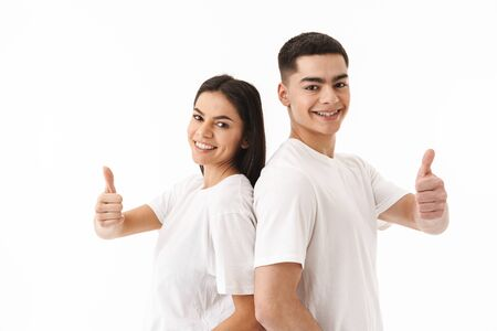 Attractive young couple standing isolated over white background, thumbs up