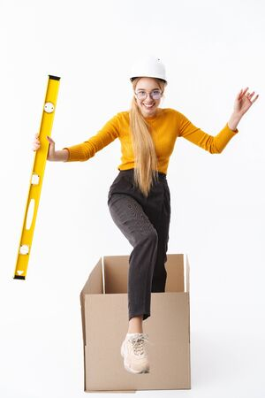 Full length of an attractive young woman architect wearing hard hat isolated over white background, showing building level while getting out from the box Stock Photo