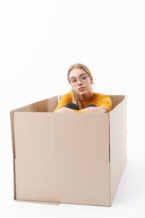 Attractive young woman sitting inside the box isolated over white background