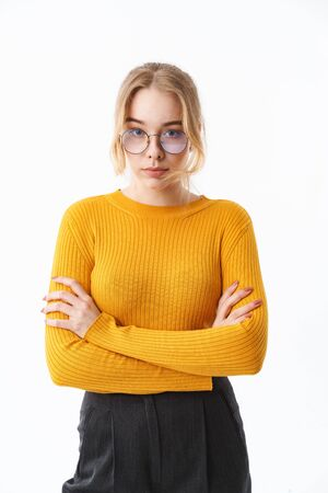 Attractive young girl wearing sweater standing isolated over white background, arms folded