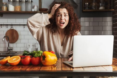 Image of nervous caucasian woman using laptop while cooking fresh vegetable salad in kitchen interior at home