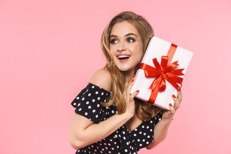 Image of a beautiful young pretty woman posing isolated over pink wall background holding present gift box.