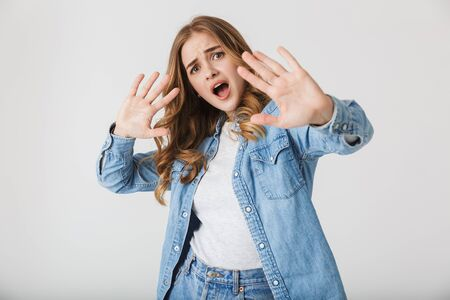 Attractive young upset girl standing isolated over white background, showing stop gesture Stock Photo