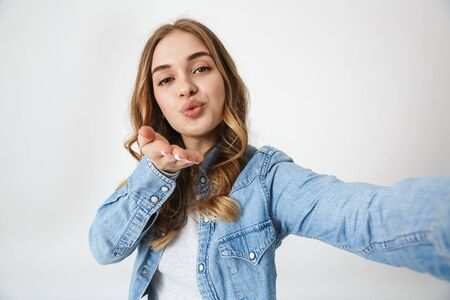 Attractive excited young girl standing isolated over white background, taking a selfie, sending kiss