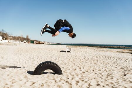 Photo of bold guy 20s in black tracksuit doing parkour and jumping during morning acrobatics by seaside