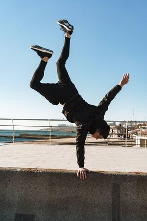 Photo of european guy 20s in black tracksuit doing acrobatics and standing on his arms during morning workout by seaside