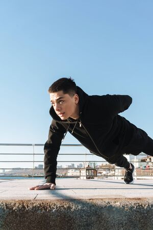 Photo of concentrated guy 20s in black tracksuit doing push ups on the floor during morning workout by seaside Reklamní fotografie