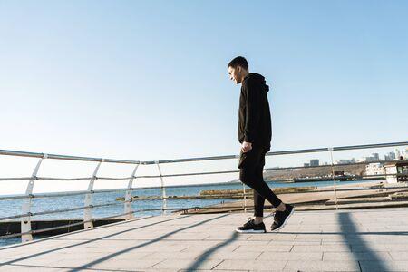 Foto di un gioioso ragazzo di 20 anni in abiti neri che cammina lungo la passerella di legno in riva al mare dopo l'allenamento mattutino