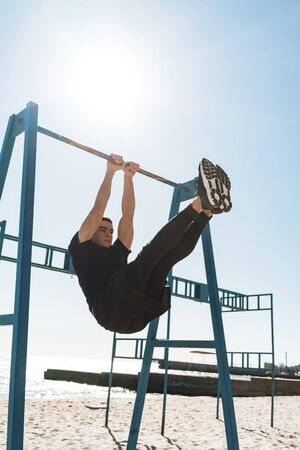 Photo of handsome guy 20s in black tracksuit doing acrobatics on horizontal gymnastic bar during morning workout by seaside Stock Photo